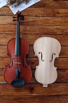Il violino e l'arco di legno sono posti accanto al violino incompiuto