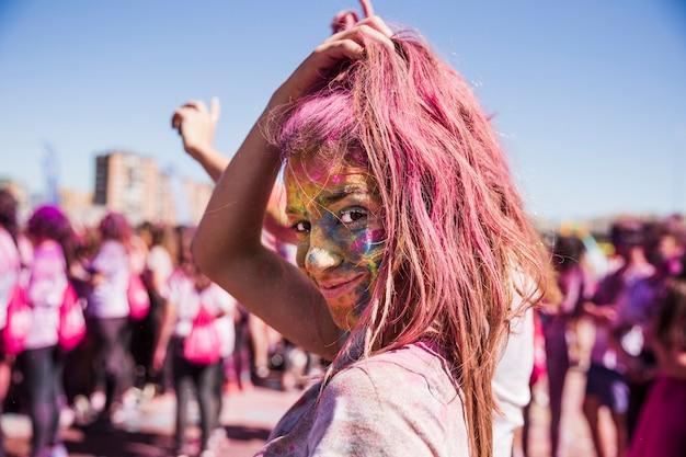 Il viso della giovane donna coperto di polvere di holi che guarda l'obbiettivo