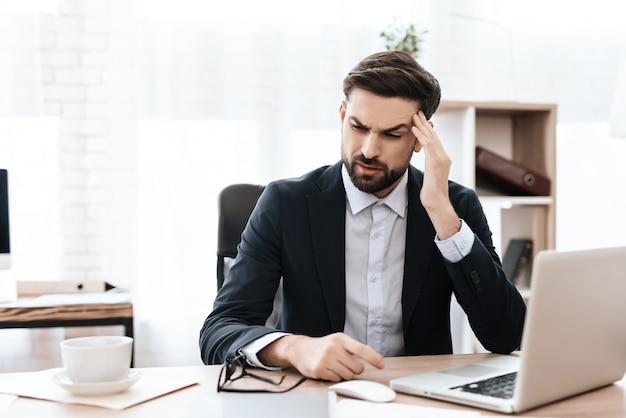 Il viso fa una smorfia di dolore. l'uomo è seduto al lavoro.