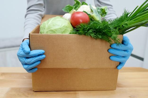 Il volontario in guanti tiene le verdure in scatola per donare cibo per aiutare i poveri. scatola di donat con prodotti alimentari