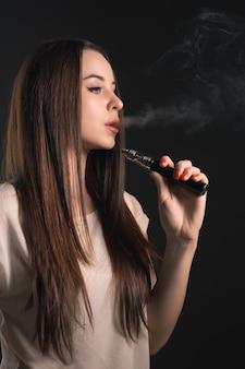 Il volto di svapare giovane donna in studio nero