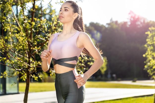 Il womanin atletico attraente l'abbigliamento sportivo sta correndo al parco il giorno soleggiato