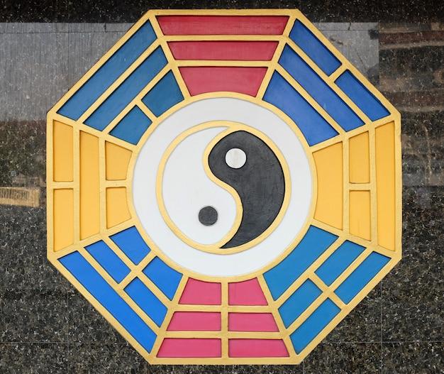 Il yin yang firma sul muro del tempio cinese in tailandia.
