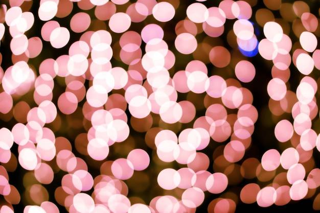 Illuminazione a led sfocato e bokeh rosa a schermo intero e sfondo nero.