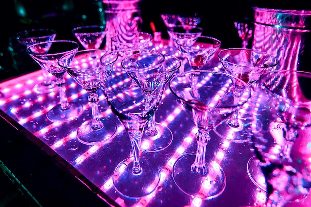 Illuminazione a raggi ultravioletti di bicchieri vuoti da cocktail drink