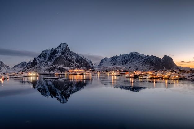 Illuminazione del villaggio di pescatori con la riflessione della catena montuosa sulla linea costiera all'alba