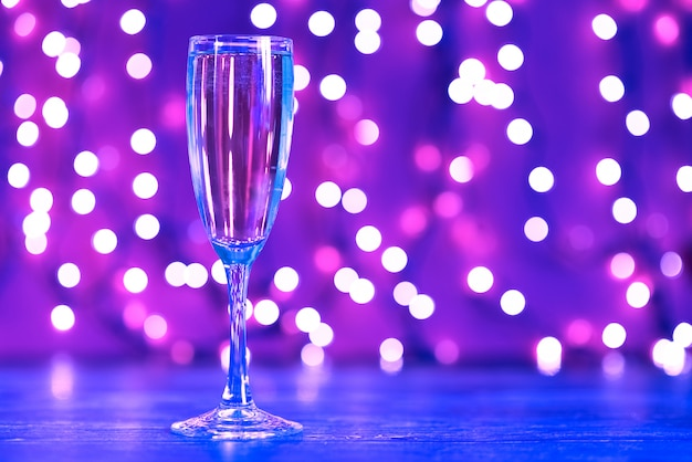 Illuminazioni natalizie e bicchiere di champagne