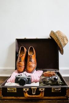 Imballando per il concetto di viaggio con i vestiti e gli accessori d'annata dei pantaloni a vita bassa in valigia sul pavimento di legno contro il fondo bianco della parete con spazio vuoto
