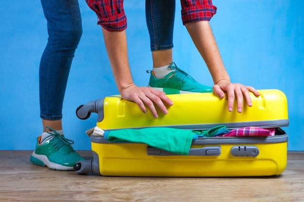 Imballare i vestiti in una valigia gialla. imballare gli articoli necessari per il viaggio o il viaggio d'affari. vacanze, vacanze. concetto di viaggio