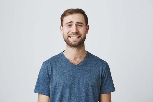 Imbarazzante bel ragazzo con la barba serrare i denti, sentirsi a disagio