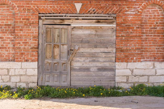 Imbarcato porta di legno in un vecchio magazzino in un muro di mattoni