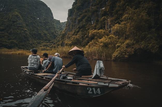 Imbarcazione a remi della donna lungo un fiume nel vietnam rurale