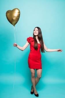 Immagine a figura intera di splendida donna in abito rosso fantasia in posa con palloncino a forma di cuore, isolato