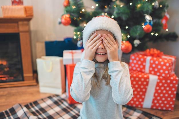 Immagine adorabile di piccola ragazza che si siede sulle ginocchia e che copre gli occhi di mani.