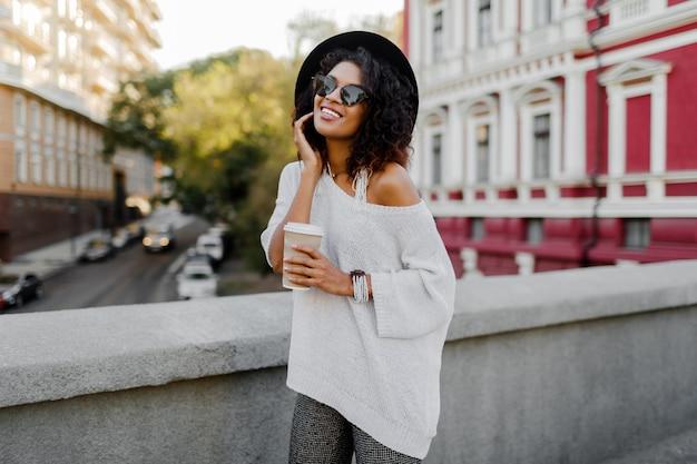 Immagine all'aperto di stile di vita dai toni morbidi della donna di colore beata che cammina nella città di primavera con una tazza di cappuccino o tè caldo. vestito hipster maglione bianco oversize, cappello nero, accessori alla moda.