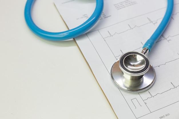 Immagine alta vicina del grafico dell'elettrocardiografia e degli stetoscopi blu.