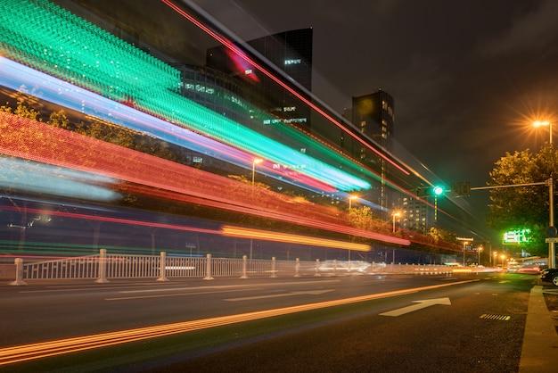 Immagine astratta del movimento della sfuocatura delle automobili sulla strada di città alla notte