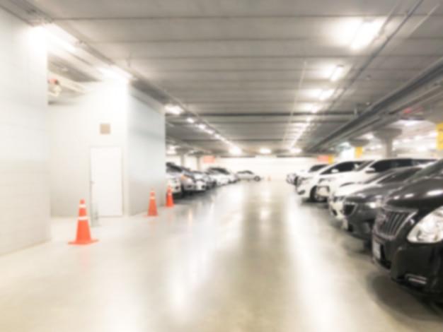 Immagine astratta della sfuocatura di molte automobili nell'interno del garage al grande magazzino o al centro commerciale