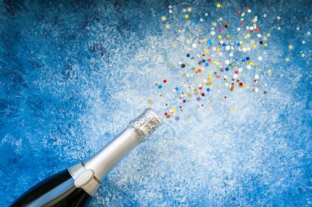 Immagine astratta di bottiglia di champagne e paillettes piana di natale, anniversario, carnevale, concetto di celebrazione di capodanno. copia spazio, vista dall'alto.
