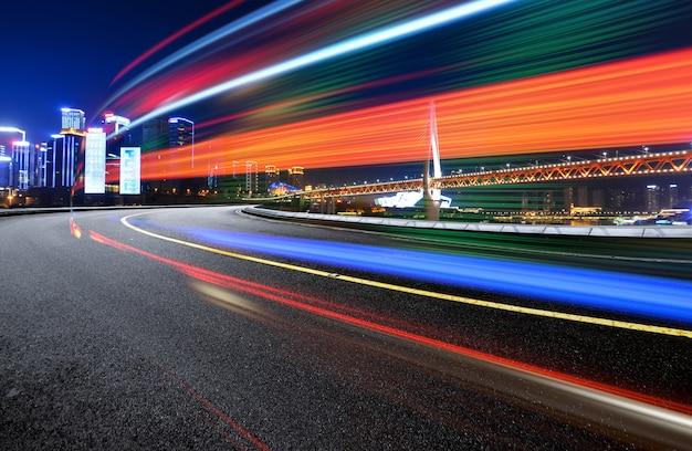 Immagine astratta di movimento della sfocatura delle automobili sulla strada di città alla notte, architettura urbana moderna a chongqing, cina