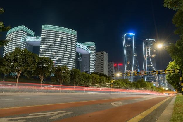 Immagine astratta di sfocatura movimento di automobili sulla strada di città di notte, architettura urbana moderna