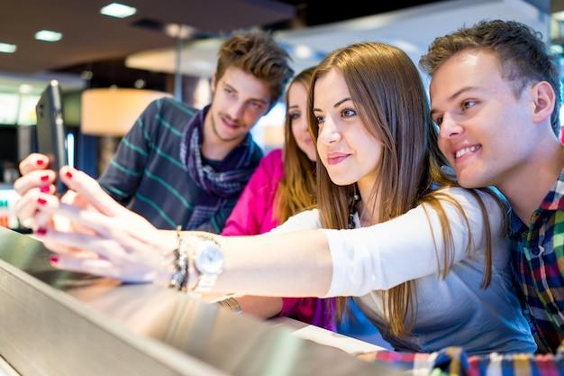 Immagine autentica di giovani persone reali che si divertono insieme usando il cellulare