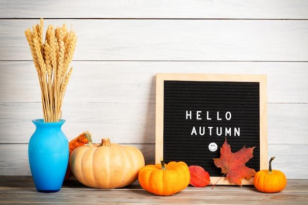 Immagine autunno natura morta con zucche, vaso con chicchi di segale, fogliame e bacheche con le parole ciao autunno contro la parete di legno bianca.