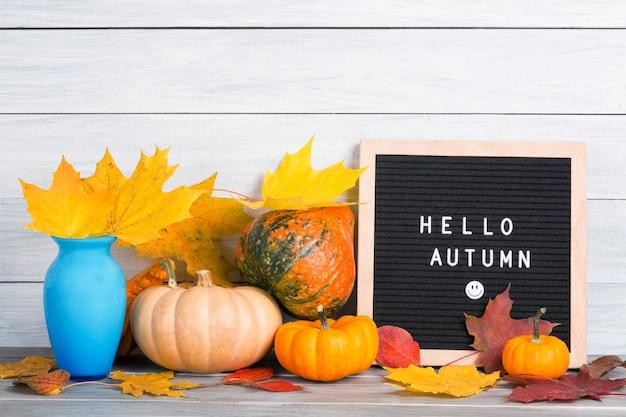 Immagine autunno natura morta con zucche, vaso con fogliame di acero colorato e bacheche con parole ciao autunno contro la parete di legno bianca.