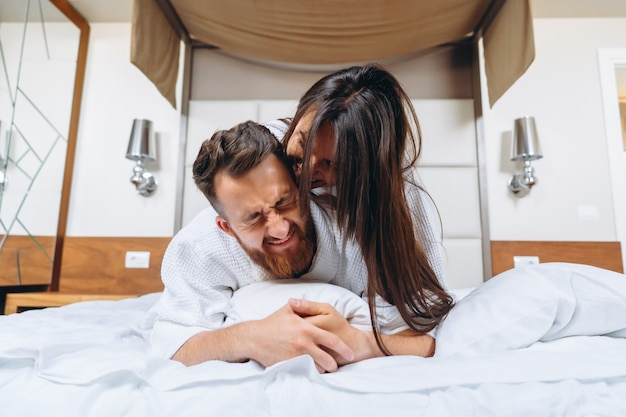 Immagine che mostra le coppie felici che riposano nella camera di albergo