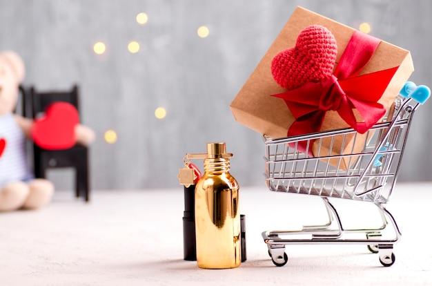 Immagine concettuale di vacanza del carrello, del contenitore di regalo e della forma del cuore, del rossetto e del profumo