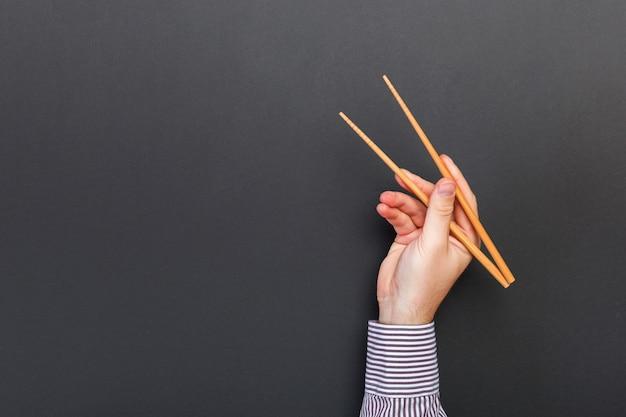 Immagine creativa delle bacchette di legno in mani maschili su sfondo nero. alimento giapponese e cinese con copyspace