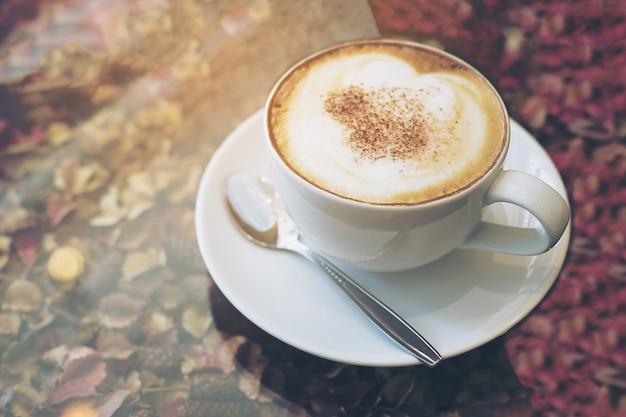 Immagine d'annata della tazza di caffè calda sulla struttura asciutta dei petali del fiore e sul piano d'appoggio di vetro