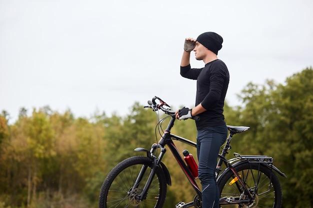 Immagine del ciclista su strada che cicla e si prepara sulla strada nella foresta.