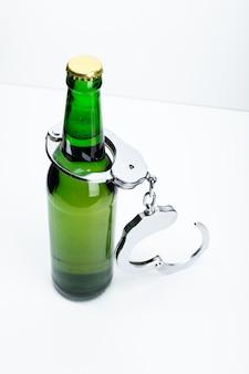 Immagine del concetto di bere illegalmente con una bottiglia di birra e un paio di manette