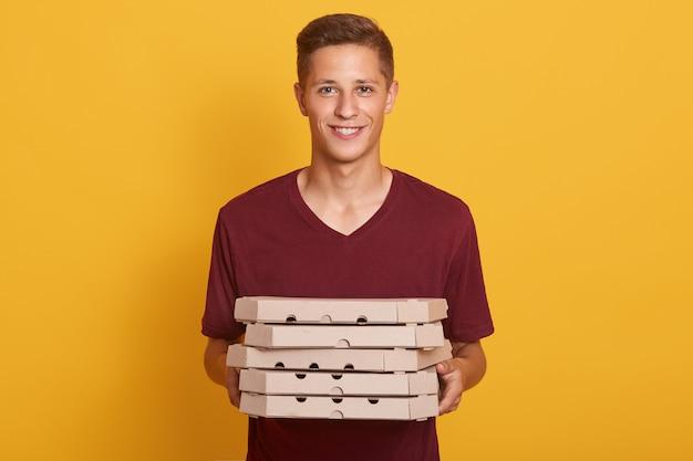 Immagine del fattorino bello allegro che porta la maglietta casuale di borgogna, tenendo la pila di scatole della pizza in mani e esaminando direttamente la macchina fotografica isolata sullo studio giallo. concetto di cibo spazzatura.