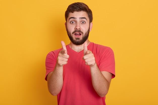 Immagine del giovane bello che sta isolato sopra giallo, esaminando macchina fotografica e indicando con le dita anteriori
