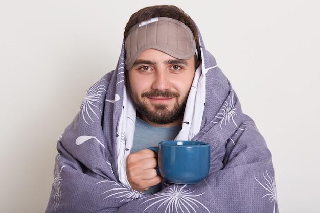 Immagine del giovane caucasico barbuto con la benda sulla fronte, maschio con la barba lunga con i baffi, che tiene tazza o tazza di caffè blu