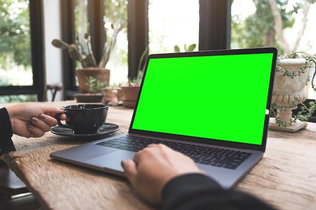 Immagine del modello della donna che utilizza e che scrive sul computer portatile con lo schermo da tavolino in bianco mentre bevendo caffè sulla tavola di legno d'annata in caffè
