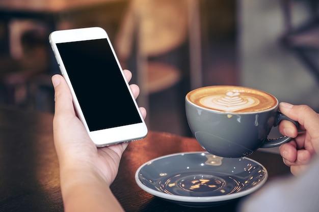 Immagine del modello delle mani che tengono il telefono cellulare bianco con lo schermo in bianco