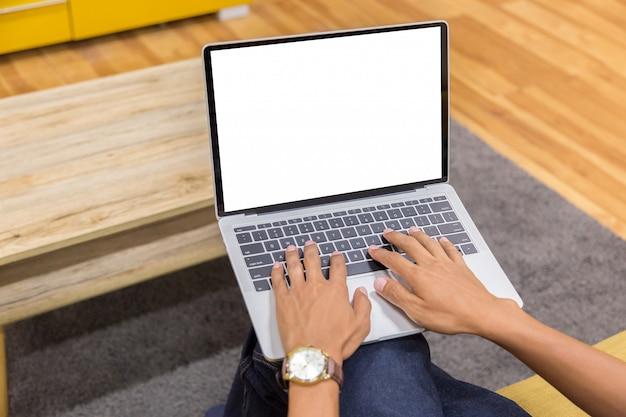 Immagine del modello di un uomo d'affari che utilizza computer portatile con lo schermo da tavolino bianco in bianco che funziona nell'immagine domestica