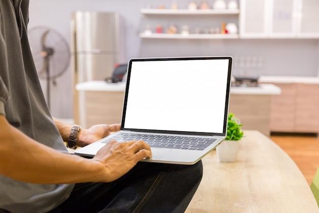 Immagine del modello di un uomo d'affari che utilizza computer portatile con lo schermo da tavolino bianco in bianco che funziona nella casa