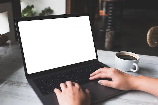 Immagine del modello di una donna che utilizza e che scrive sul computer portatile con lo schermo bianco in bianco e la tazza di caffè sulla tavola in caffè moderno