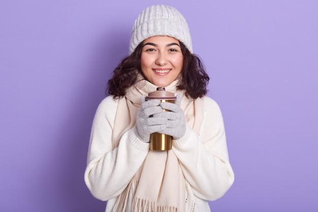 Immagine del modello grazioso sorridente ispirato con capelli ricci scuri che tengono tazza termica, essendo di buon umore, trascorrendo del tempo da soli in studio