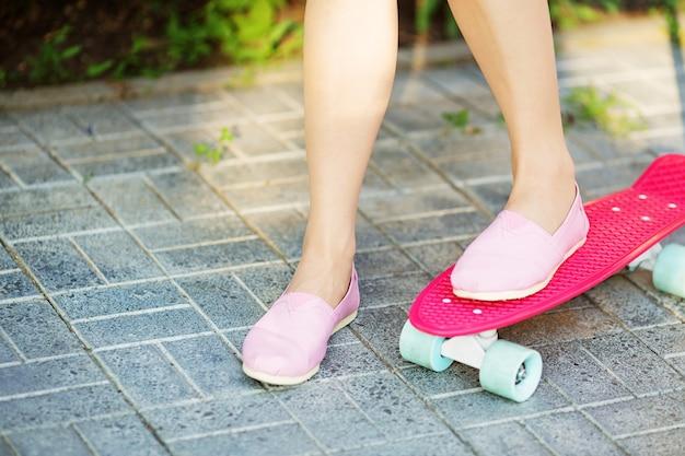 Immagine del primo piano dei piedi femminili allo skateboard