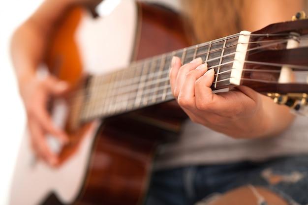 Immagine del primo piano della chitarra in mani della donna