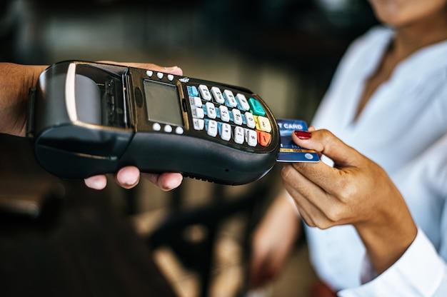 Immagine del primo piano della donna che paga con la carta di credito in caffè