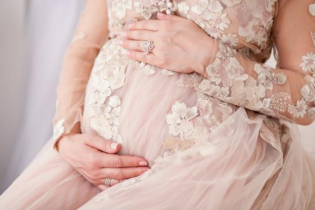 Immagine del primo piano della donna incinta che tocca la sua pancia con le mani. abito in tulle beige