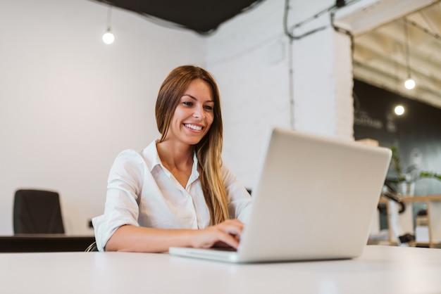 Immagine del primo piano della giovane donna sorridente che utilizza computer portatile nello studio creativo luminoso.