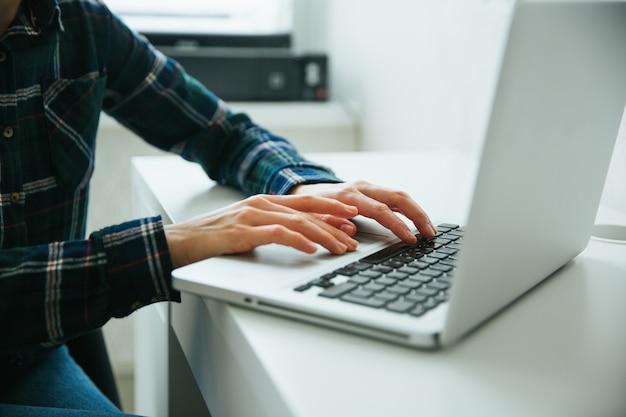 Immagine del primo piano della mano usando e digitando sulla tastiera del computer portatile