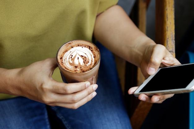Immagine del primo piano delle mani del maschio o della donna facendo uso dello smartphone al caffè mentre bevendo caffè